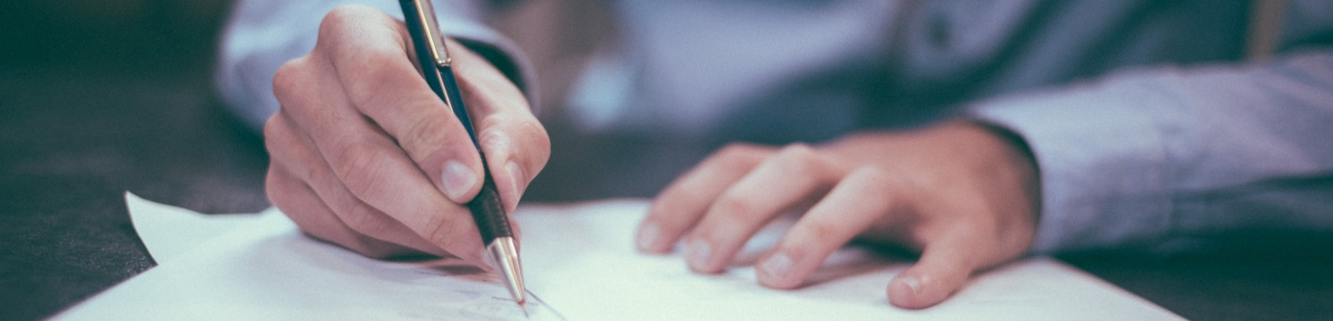 A business man using a ballpoint pent to write on paper